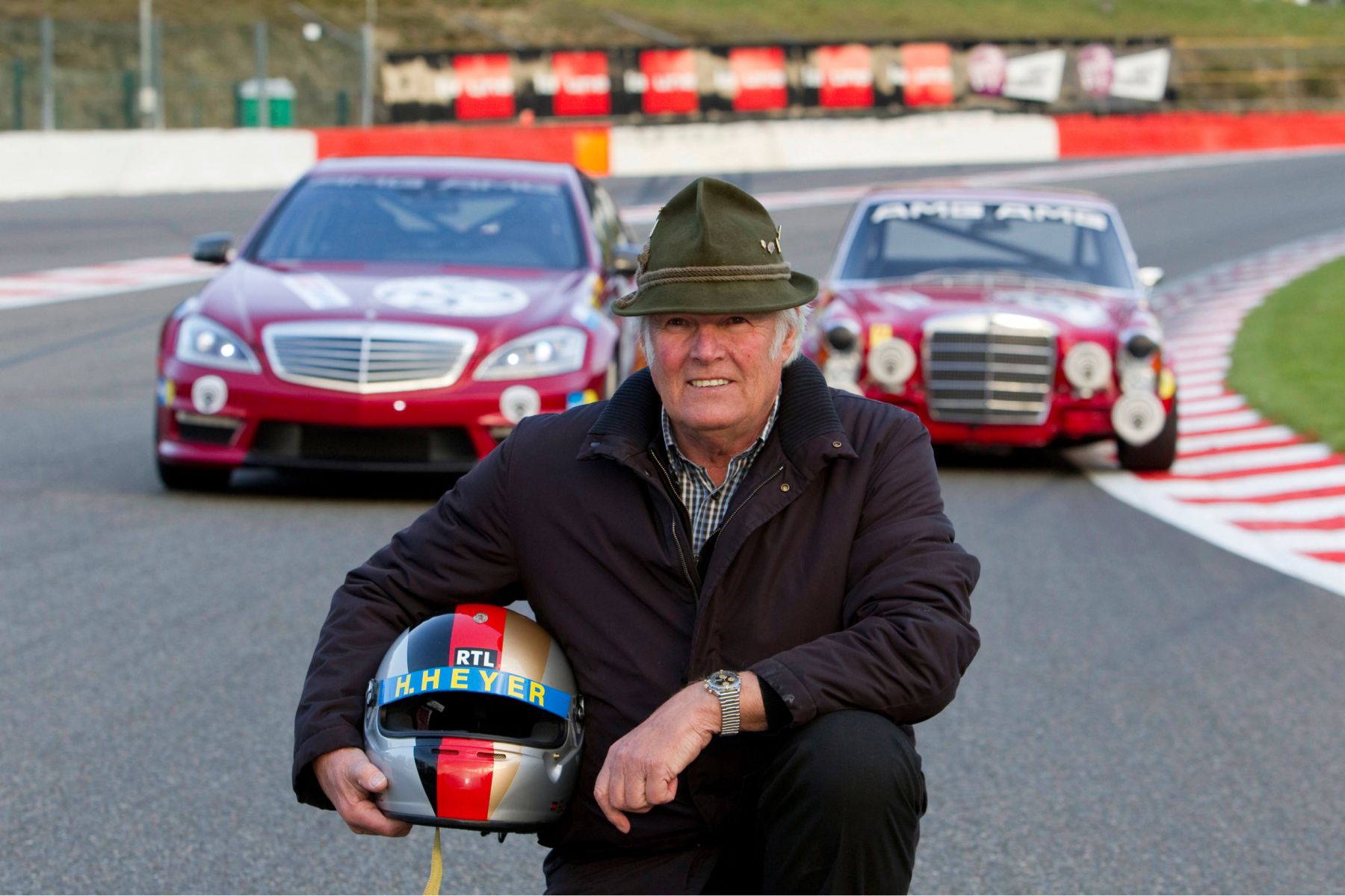 """Hans Heyer, one of the drivers of the successful AMG 300 SEL 6.8 racing touring car of 1971 in Spa-Francorchamps. In the background, to the left, the vehicle as a detailed reconstruction from 2006 (right) along with the Mercedes-Benz S 63 AMG """"Thirty-Five"""" (W 221) with a decal based on the racing touring car. Photo from 2010."""